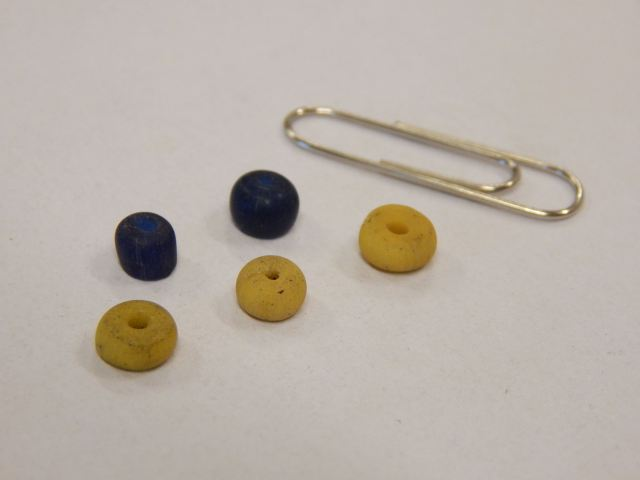 Blue and yellow drawn beads of early Islamic glass.