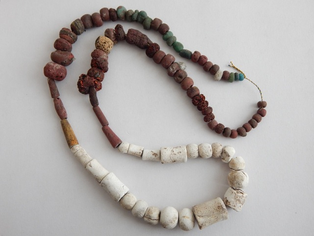 Necklace beads of glass and fossil from Ire Grave 133B.